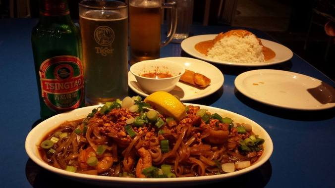 Foreground: Tsingtao, Pad Thai.  Background: Singha, spring roll, and spicy peanut chicken and rice.